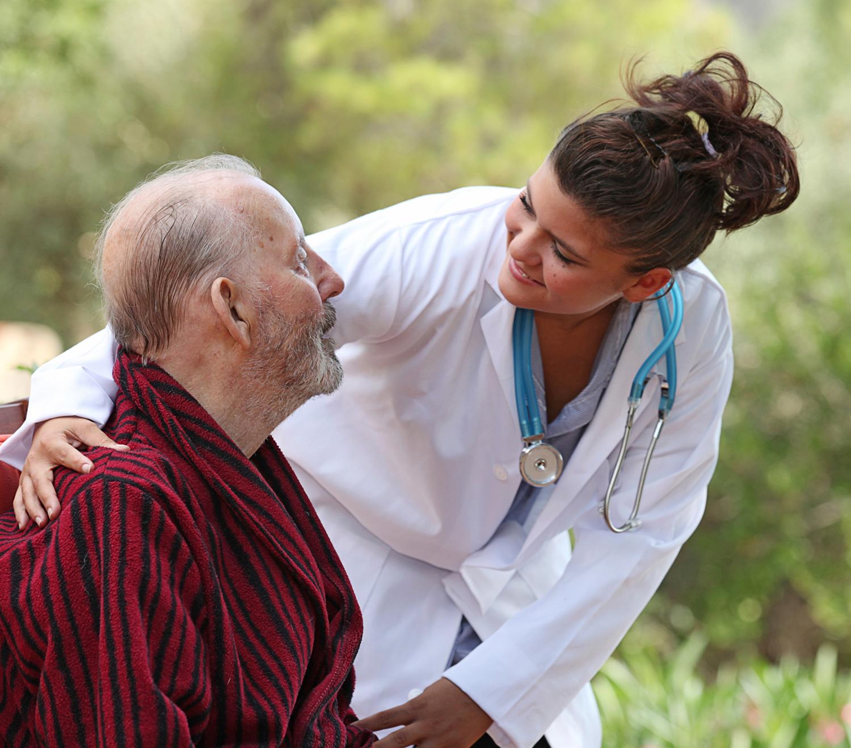 une jeune femme médecin à l'écoute d'un sénior dans un jardin